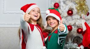 Children cheerful celebrate christmas. Kids christmas costumes santa and elf. Winter masquerade concept. Siblings ready. Celebrate christmas or meet new year stock image