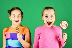 Children with cheerful faces pose with candies on green. Background. Sisters with round and long shaped lollipops. Girls eat big colorful sweet caramels royalty free stock photo