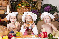 Children in a chef\'s hats eating bread. Children in a chef\'s hats looking and eating bread Royalty Free Stock Photos