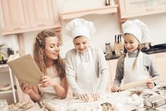 Children with mother in kitchen. Brother is kneading dough. Children in chef`s hats with mother in kitchen. Brother is kneading dough royalty free stock photos