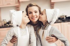 Children with mother in kitchen. Brother and sister are kissing mother on cheeks. stock photo