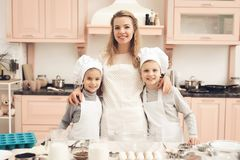Children with mother in kitchen. Family is going to cook. Children in chef`s hats with mother in kitchen. Family is going to cook Royalty Free Stock Image