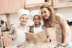 Children with mother in kitchen. Family is reading recipe in cookbook. Children in chef`s hats with mother in kitchen. Family is reading recipe in cookbook Royalty Free Stock Photos