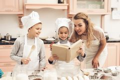 Children with mother in kitchen. Family is reading recipe in cookbook. Children in chef`s hats with mother in kitchen. Family is reading recipe in cookbook Stock Photos