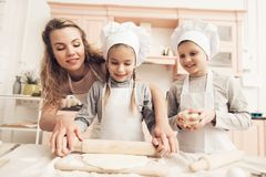 Children with mother in kitchen. Mother is helping kids to roll out dough. Children in chef`s hats with mother in kitchen. Mother is helping kids to roll out stock images