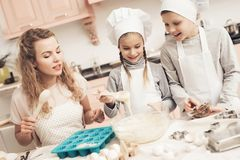 Children with mother in kitchen. Mother is teaching kids how to put dough in baking dish. Children in chef`s hats with mother in kitchen. Mother is teaching Stock Photo