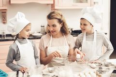 Children with mother in kitchen. Mother is teaching kids how to break eggs. royalty free stock images