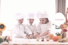 Children in the chef`s uniform make cookies standing at the kitchen table. The concept of a hobby royalty free stock image