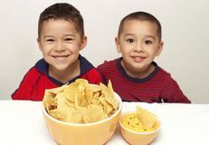 Children and chips. Two brothers ready to enjoy a snack of tortilla chips and queso royalty free stock images