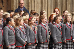 Children choir singing Christmas carols in front of the Bath Abbey. School children choir singing Christmas carols in front of the Bath Abbey in Bath, England Stock Image