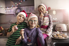 Children with Christmas cookies in a kitchen stock images