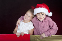 Children in christmas hat in present boxes. Girl and boy in christmas hat in present boxes Stock Photography