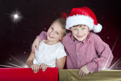Children in christmas hat in present boxes. Girl and boy in christmas hat in present boxes Stock Images