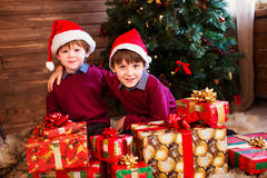 Children in Christmas hat with presents in a house. Children in Christmas hat with presents in a house near the Christmas tree Stock Photos