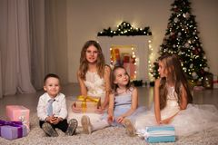 Children at Christmas sparklers new year gifts. Kids boy and three girls at Christmas sparklers new year gifts stock photography