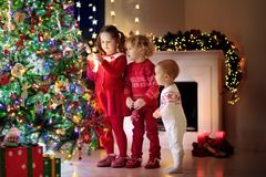 Children at Christmas tree. Kids at fireplace on Xmas eve. Children at Christmas tree and fireplace on Xmas eve. Family with kids celebrating Christmas at home Royalty Free Stock Photo