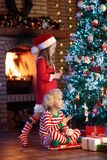 Child at Christmas tree. Kids at fireplace on Xmas. Children at Christmas tree and fireplace on Xmas eve. Family with kids celebrating Christmas at home. Boy and royalty free stock images