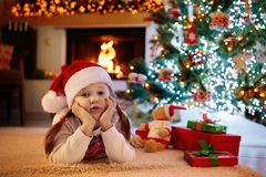 Child at Christmas tree. Kids at fireplace on Xmas. Children at Christmas tree and fireplace on Xmas eve. Family with kids celebrating Christmas at home. Boy and stock photography