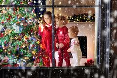 Children at Christmas tree. Kids at fireplace on Xmas eve. Children at Christmas tree and fireplace on Xmas eve. Family with kids celebrating Christmas at home Stock Image