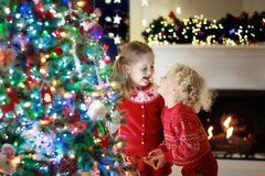 Children at Christmas tree. Kids at fireplace on Xmas eve stock photo