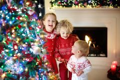 Children at Christmas tree. Kids at fireplace on Xmas eve. Children at Christmas tree and fireplace on Xmas eve. Family with kids celebrating Christmas at home royalty free stock images