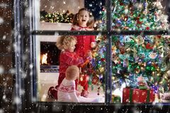 Children at Christmas tree. Kids at fireplace on Xmas eve. Children at Christmas tree and fireplace on Xmas eve. Family with kids celebrating Christmas at home royalty free stock photography