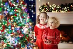 Children at Christmas tree. Kids at fireplace on Xmas eve. Children at Christmas tree and fireplace on Xmas eve. Family with kids celebrating Christmas at home Stock Photos