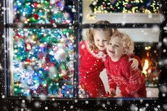 Children at Christmas tree. Kids at fireplace on Xmas eve. Children at Christmas tree and fireplace on Xmas eve. Family with kids celebrating Christmas at home stock images
