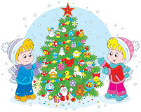 Children and Christmas tree. Little girl and boy decorating a green fir to the Holiday Royalty Free Stock Photos