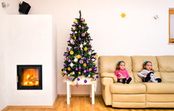 Children and Christmas tree in modern luxury apartment with fire Stock Photography
