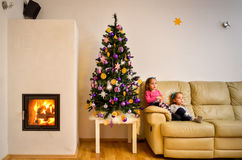 Children and Christmas tree in modern luxury apartment with fire Stock Image