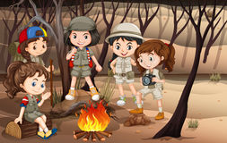 Children circle around the campfire in the woods Royalty Free Stock Photography