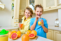 Children with citrus. Boys drink fresh orange Royalty Free Stock Photos