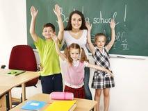 Children in classroom near blackboard. Stock Photos