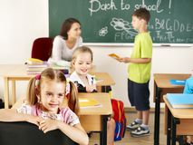 Children in classroom near blackboard. Stock Photos
