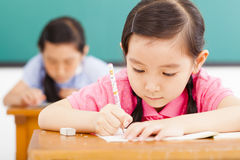 Children in classroom with pen in hand Stock Images