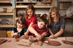 Children in a clay studio. Four children working on crafts in a clay studio royalty free stock photo