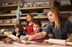 Children in a clay studio. Four children working on crafts in a clay studio stock photo