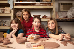 Children in a clay studio. Four children working on crafts in a clay studio with funny expressions stock photo