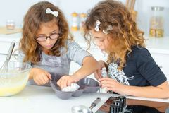 Children cleaning cake mold. Adorable stock photo