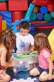 Children cleaning up toys in box Stock Images