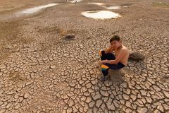 Children and climate change drought impact and water crisis. Children and climate change, Drought impact and water crisis. Sad child sitting at empty drought stock photography
