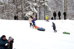 Children climb a snow hill. Winter fun. The action takes place on the outskirts of the city of Monino. Residents of the town come with children on a snow hill royalty free stock photography