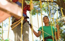 Children climbing in adventure park. Summer camp. Children climbing in adventure park outdoors. Summer camp royalty free stock images