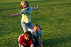Children climbing on each other at park. Natural image of three children at park Stock Photo
