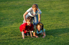 Children climbing on each other at park. Natural image of three children at park Royalty Free Stock Image