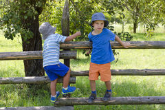 Children climbing garden fence Stock Images