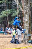 Children climbing trees in a harness. New Carlisle Indiana USA , March 17, 2019; During  sugar camp days at Bendix woods county park children in a harness learn royalty free stock image