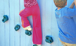 Children on Climbing Wall. Boy and girl on rock climbing wall at playground Stock Photos