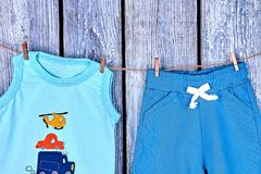 Children clothes hanging on rope. Baby boy cotton t-shirt and shorts drying on clothesline on vintage wooden background Royalty Free Stock Photography